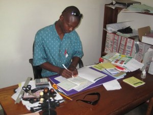 An employee at FECECAV, a Togolese MFI, tracking loan repayments by hand. Many of FECECAV's branches operate without electicity.