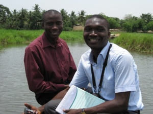 Jacques, WAGES' Kiva Coordinator, and a colleague taking a boat to visit a Kiva client in a rural area.