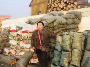 Kiva entrepreneur selling bags of wood and coal