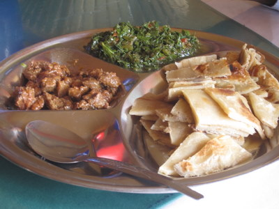 Three of Kenya's staple foods: chapatti (flat bread made of wheat flour, water, and salt), sukuma wiki (chopped kale & collard greens), and grilled meat