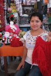 Kiva Borrower Marisela shows off her Christmas wares, including dolls, shawls and hats. She crochets all the fabrics herself and makes the dolls by hand.