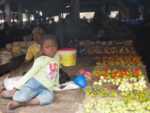 A Young Girl Selling Vegetables At The Market