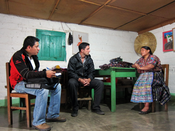 Juan Carlos and I listening to a borrower tell her story