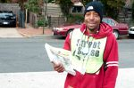 a homeless magazine vendor with an established brand behind him