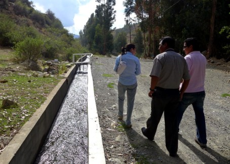 CIDRE loan officers alongside a community irrigation canal which serves Kiva borrowers